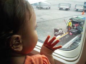 Lucia looking out the airplane window. She is ever ready for an adventure.