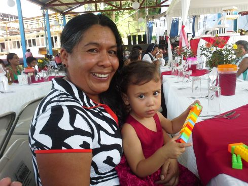 Lucia and her abuela at the wedding. Notice on the table there are pots of fresh flowers for people to take home,